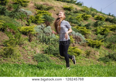 Photo of happy long-haired young blonde woman doing running activities.** Note: Soft Focus at 100%, best at smaller sizes