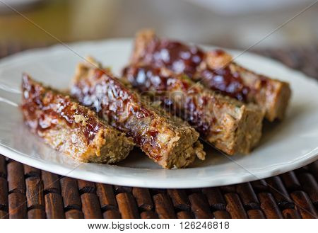 Plate of sliced homemade meatloaf with BBQ sauce topping