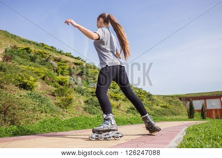 Beautiful teenage girl rollerskating in summer park.** Note: Soft Focus at 100%, best at smaller sizes