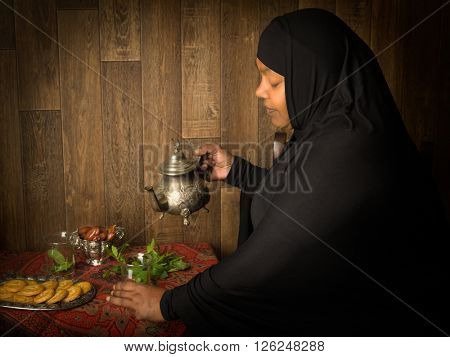 Smiling muslim woman pouring mint tea the traditional way