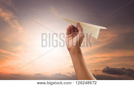 hand preparing to throwing paper plane to mid air againt green grass field and heart shape white clouds on clear blue sky