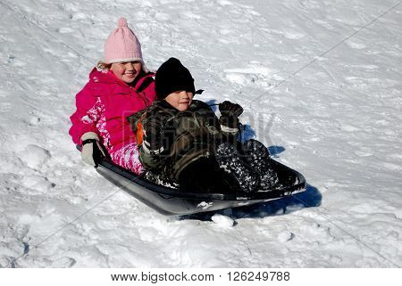 Boy and girl riding down a snow hill on a sled.
