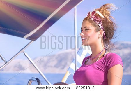Portrait of beautiful woman driving a boat in bright sunny day, enjoying sea cruise on luxury sail boat, active lifestyle, summer vacation concept