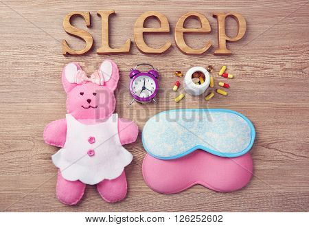 Word Sleep with pills, little toy and sleeping masks on a wooden background