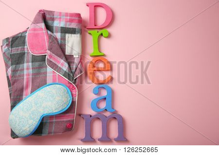 Word DREAM, sleeping mask and pajamas on pink background