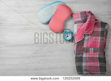 Sleeping masks, pajamas and alarm clock on wooden table, top view