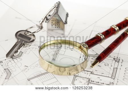 key with keychain in the form of a silver-colored house on a background of architectural drawing, pen &  magnifying glass