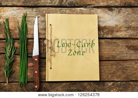 Text Low-Carb Zone in recipe book on wooden background