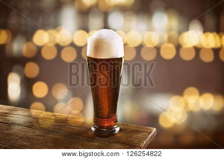 Glass of cold fresh beer on table, on dark pub background