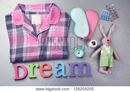Word Dream with pajamas, little toy and masks on a grey background