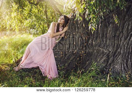 Beautiful Young Woman In A Fantasy Dress Lying On A Big Tree