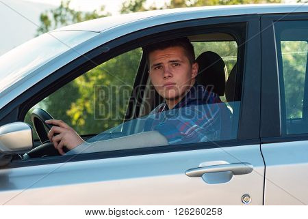 Young Adult Sitting In His Car And Looking To Camera Throught Window Door.