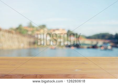 Wooden board empty table in front of blurred background. Perspective brown wood over blur wooden bridge - can be used mock up for display or montage your products. spring season. vintage filtered.