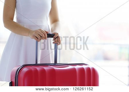 Woman in white dress holding a large red suitcase, close up