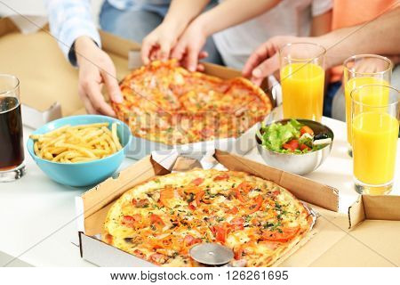 Happy family hands eating pizza.
