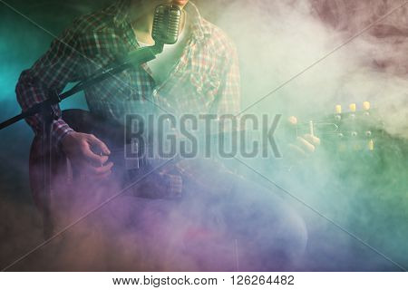Young man with microphone playing electric guitar on lighted foggy background