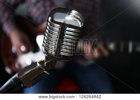 Microphone and young man playing electric guitar on dark background