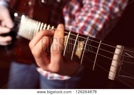 Young man playing electric guitar, close up