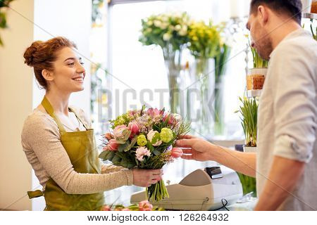 people, shopping, sale, floristry and consumerism concept - happy smiling florist woman making bouquet for and man or customer at flower shop