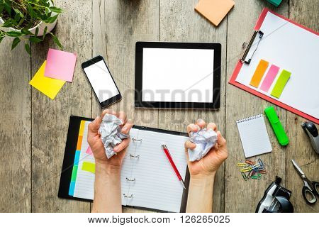Businessman hands holding creased papers. Other things around. Concept of business in modern hipster office