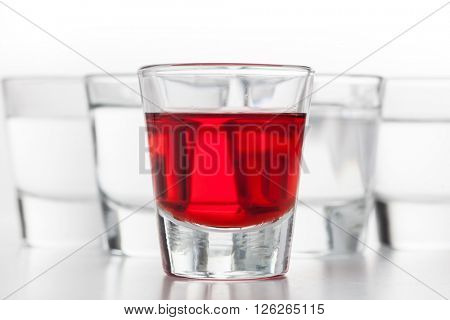 Glasses of alcohol. One red flavoured, the others clean vodka. White background.