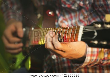 Young man playing electric guitar on lighted background