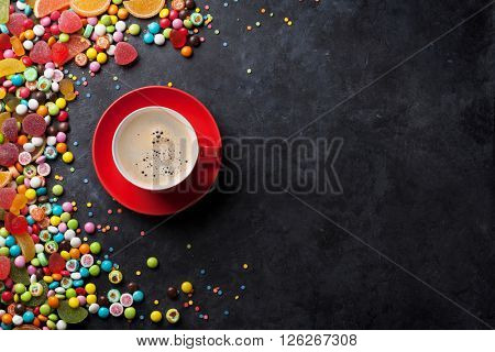 Colorful candies, jelly and marmalade and coffee cup on stone background. Top view with copy space