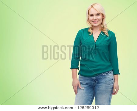 female, gender, portrait, plus size and people concept - smiling young woman in shirt and jeans over green natural background