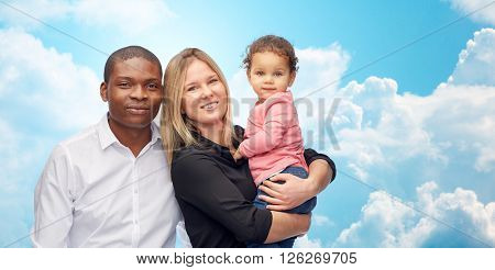 family, children, race and international concept - happy multiracial mother, father and little child over blue sky and clouds background