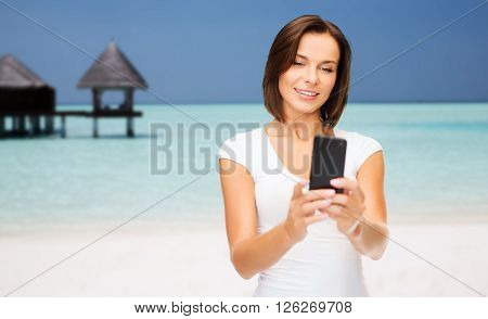 travel, tourism, summer vacation, technology and people - happy young woman taking selfie picture by smartphone on maldives beach with bungalow background