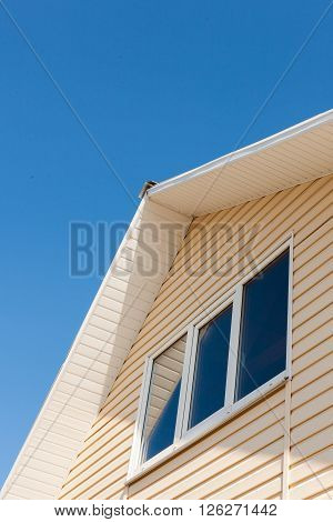 A low angle view of roof upper floors of a house in daytime against blue sky