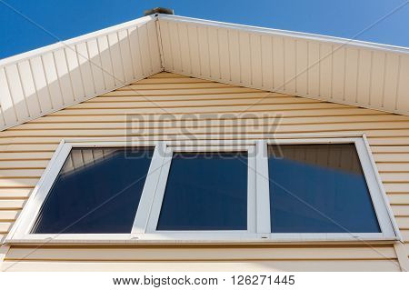 A low angle closeup view of roof upper floors of a house in daytime against blue sky