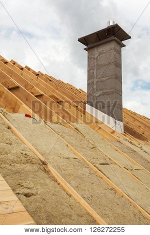 Roof insulation (rockwool). New house under construction with chimney
