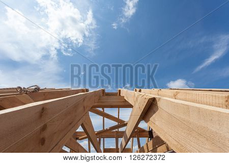 New residential wooden construction home framing against a blue sky