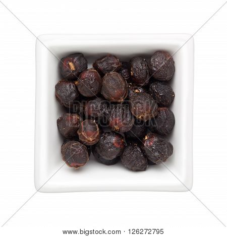 Traditional Chinese Medicine - Dried longan fruit in a square bowl isolated on white background