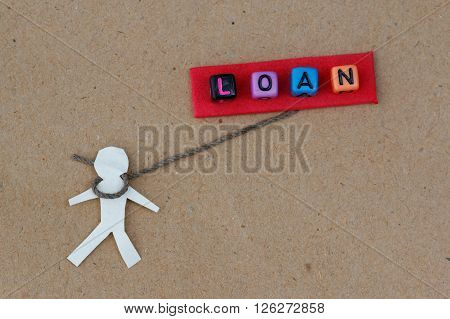 Human cut out with rope around its neck with text LOAN. Concept of human being chained by loan and financial crisis.