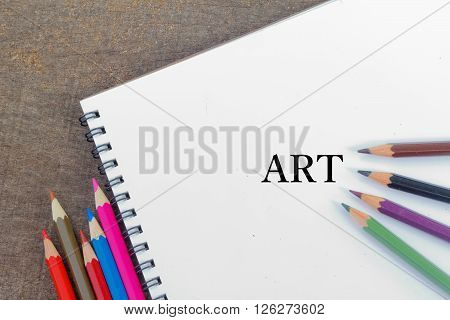 Blank notepad and colorful pencils on the wooden table. View from above. With word ART.