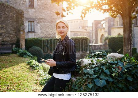 Young hipster girl in fashionable clothes and rucksack on back is posing for camera with mobile phone in hands. Cute woman in good mood is using cell telephone for chat with friends in social network