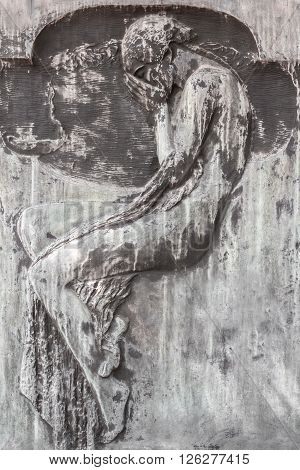 Ancient sculpture depicting a weeping man in necropolis.