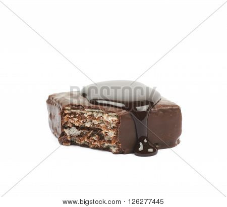 Chocolate waffle candy bar, bitten and coated with the hot chocolate, composition isolated over the white background