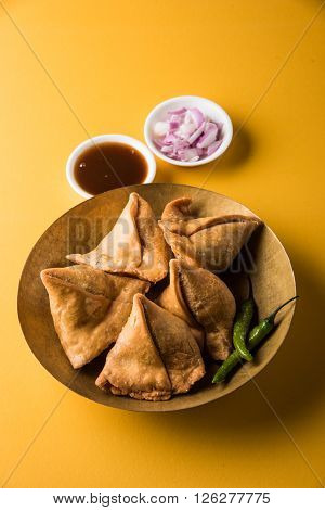 samosa snack with imli chutney or tamarind sauce, onion and green fried chili, served in a wooden bowl