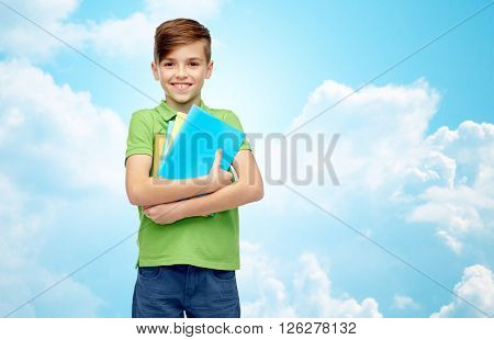 childhood, school, education and people concept - happy smiling student boy with folders and notebooks over blue sky and clouds background