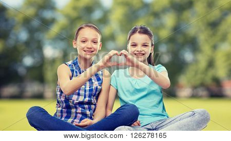 people, children, friends and friendship concept - happy little girls sitting and showing heart shape hand sign over summer park background
