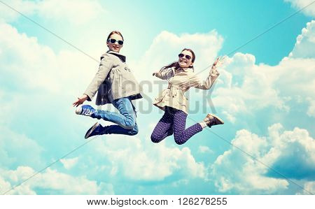 people, children, friends and friendship concept - happy little girls jumping high over blue sky and clouds background