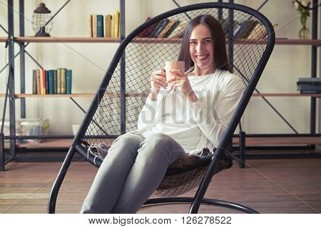 Young caucasian brunette with wide smile sitting in a designer chair with a cup