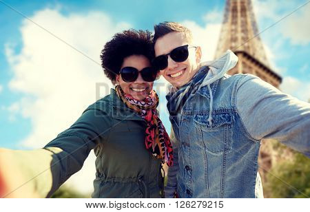 tourism, travel, people, leisure and technology concept - happy international teenage couple taking selfie over paris eiffel tower background