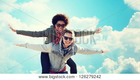 friendship, leisure, freedom and people concept - happy international teenage couple in shades having fun over blue sky and clouds background