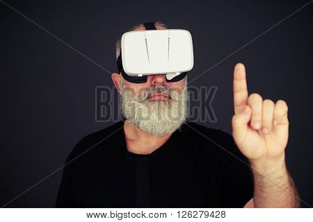 Senior man touch something with his left hand using virtual reality glasses, on black background