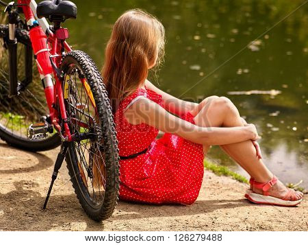 Bikes cycling girl into park. Girl sits leaning on  bicycle on shore.