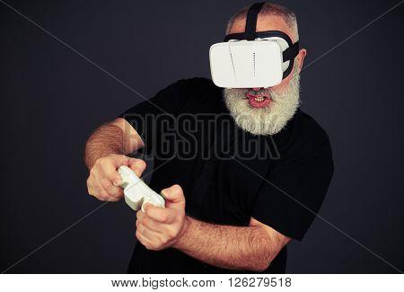 Beard senior man is playing on the joystick using virtual reality glasses, on black background